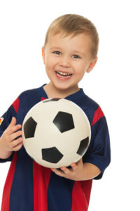 Portrait of a cheerful little boy football player in a striped uniform. The boy holds a hand soccer ball. Close-up - Isolated on white background